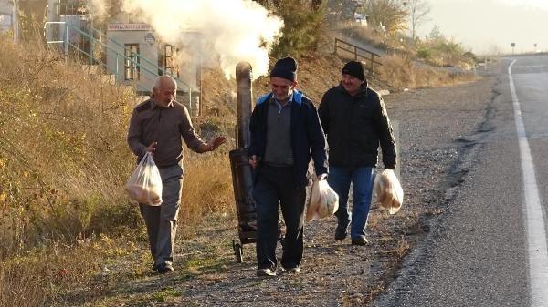 Ekmek almak için bekledikleri durakta seyyar soba ile ısınıyorlar